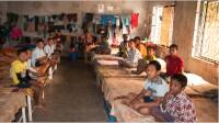 Chlapci zdětského domova Bethany veskromně zařízené ložnici.
