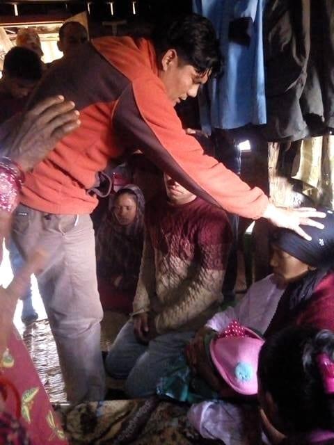 Terénní duchovní pracovník se modlí za nemocnou ženu.