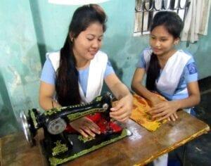 Dvě děvčata šijí na šicím stroji.